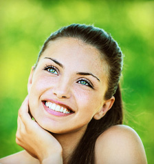 Woman showing off her beautiful dental crown in Palm Beach Gardens